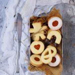 Biscotti di pasta frolla senza glutine con farine naturali ripieni di marmellata di albicocche e ricoperti di zucchero a velo e cioccolato fondente