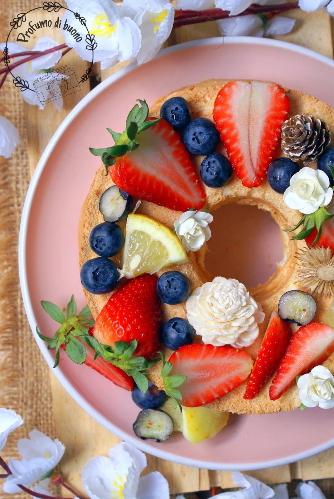 Angel food cake senza glutine servita con fragole, mirtilli e fiori eduli