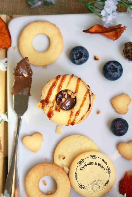 Biscotti di frolla senza glutine ripieni di crema di nocciole e coperti da una colata di caramello e granella di nocciole