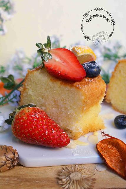 Ciambella al limone senza glutine servita con zucchero a velo, fragole e mirtilli freschi