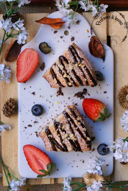 Ciambella di albumi e yogurt senza glutine servita con cioccolato fuso, granella di nocciole e fragole fresche