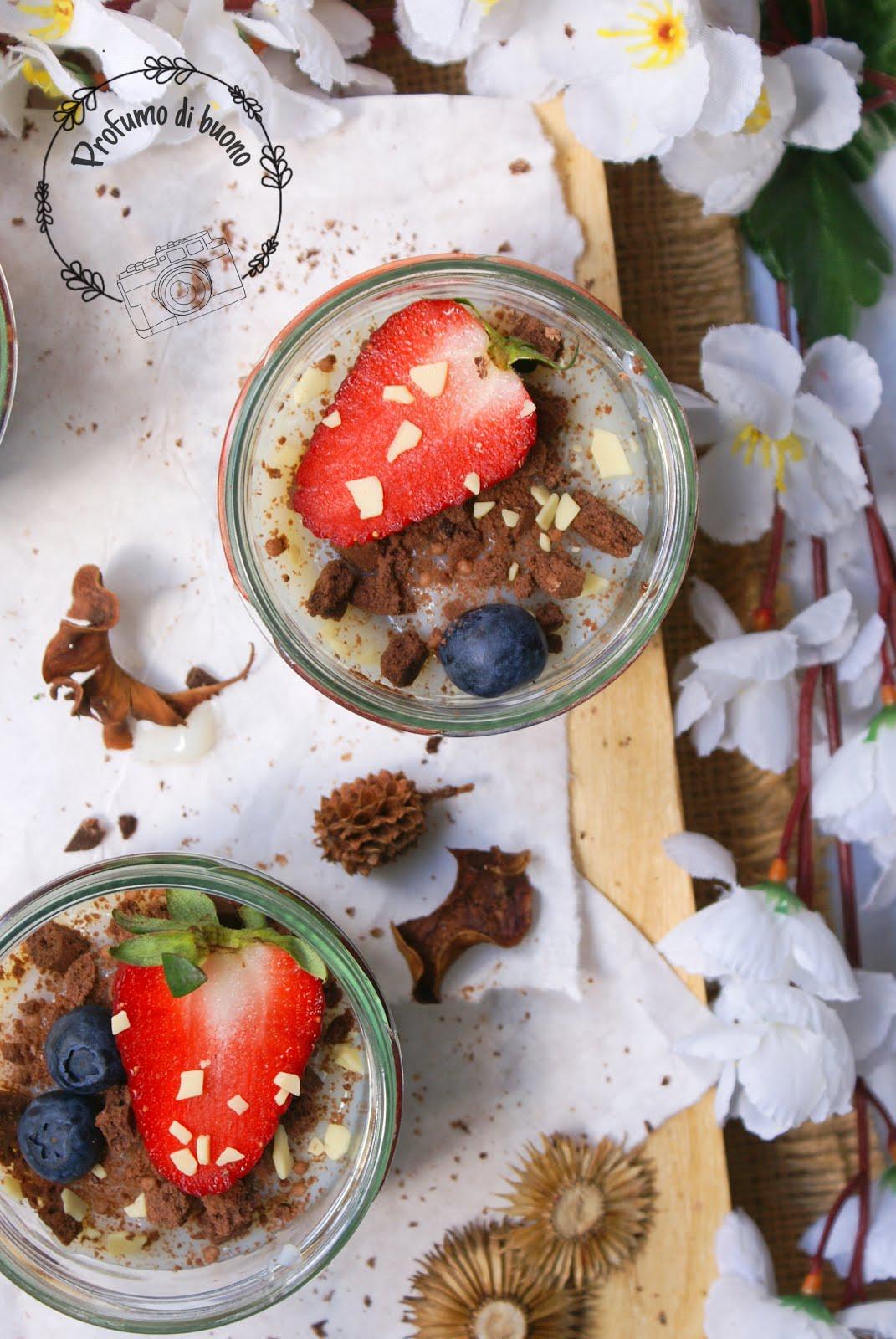 Dolci in vasetti bicolore con crema al latte decorati con mirtilli, fragole, briciole di biscotti al cacao e scagliette di cioccolato bianco