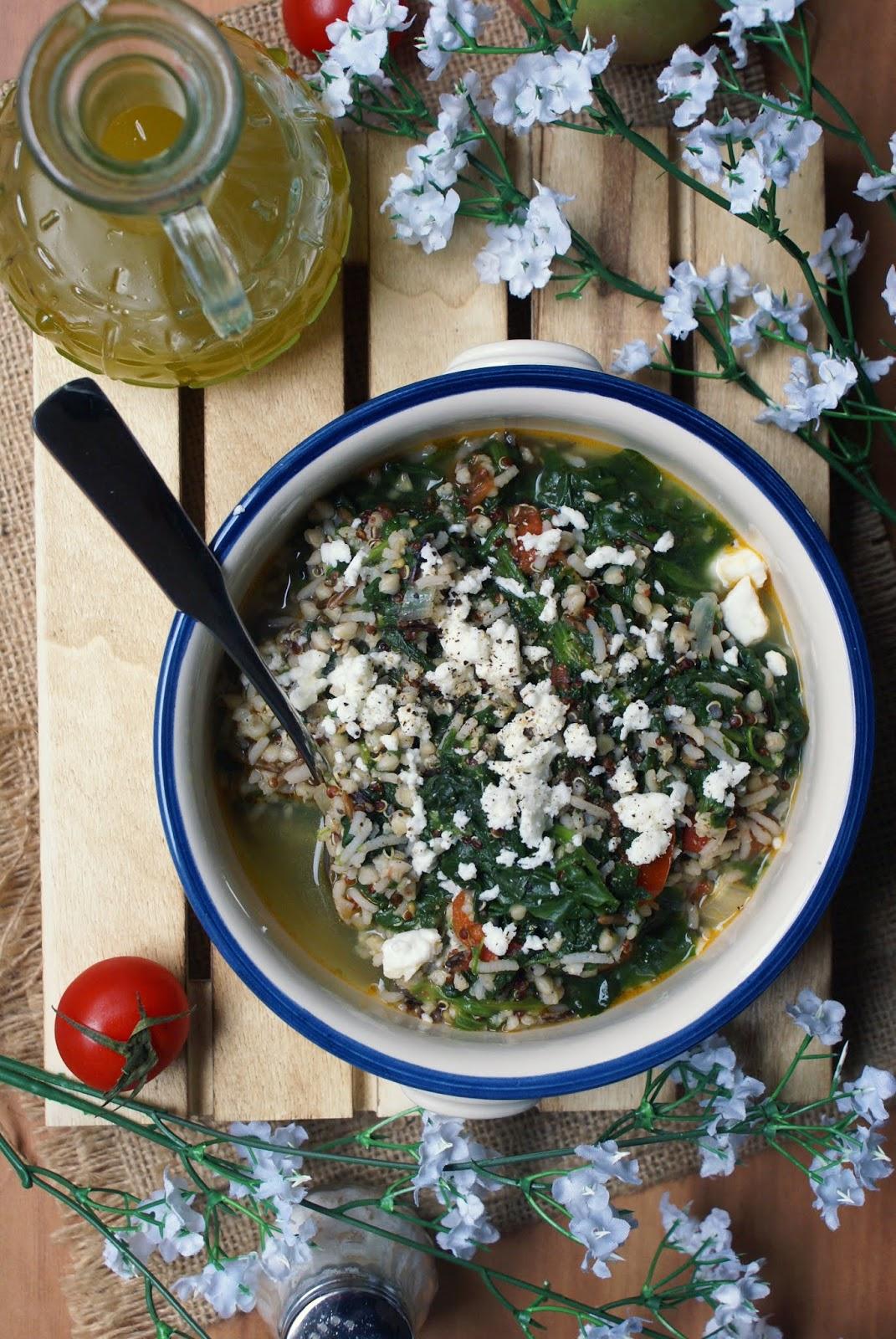 Minestra di spinaci e cereali antichi servita con formaggio feta e pepe nero macinato