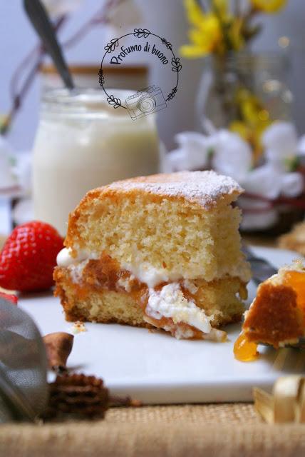 Fetta di Victoria Sponge Cake senza glutine con farine naturali farcita con crema di yogurt e panna e marmellata di albicocche. Servita con una spolverata di zucchero a velo e fragole fresche.