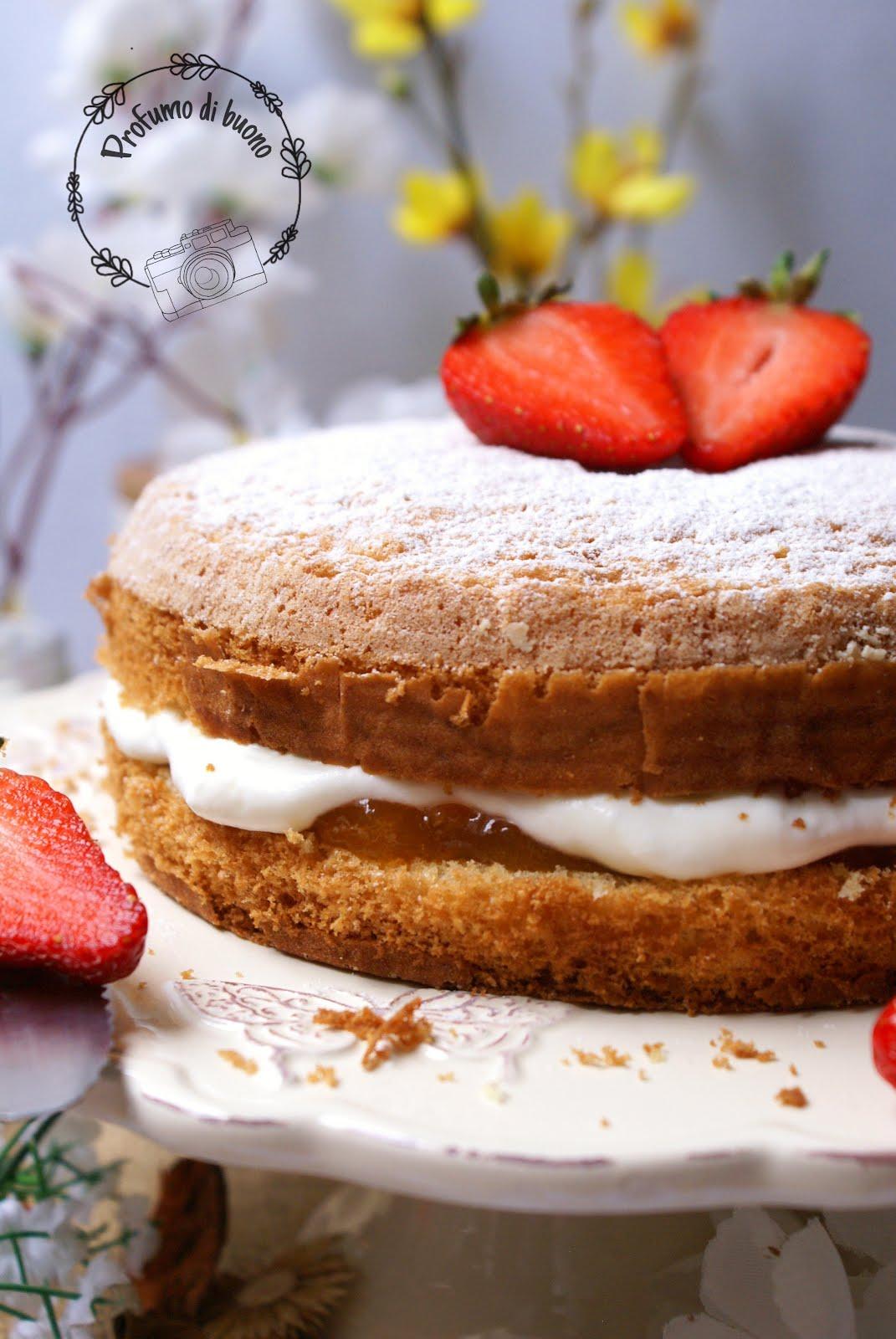 Victoria Sponge Cake senza glutine con farine naturali farcita con crema di yogurt e panna e marmellata di albicocche. Servita con una spolverata di zucchero a velo e fragole fresche.