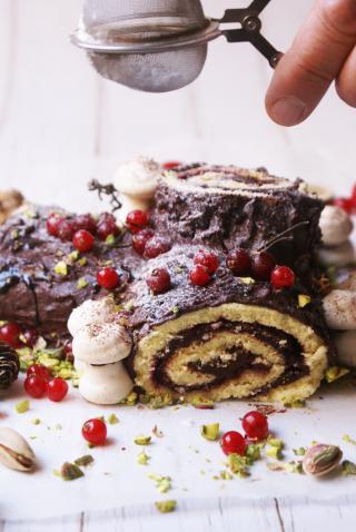 Tronchetto di Natale senza glutine ricoperto di ganache al cioccolato, zucchero a velo e ribes rosso