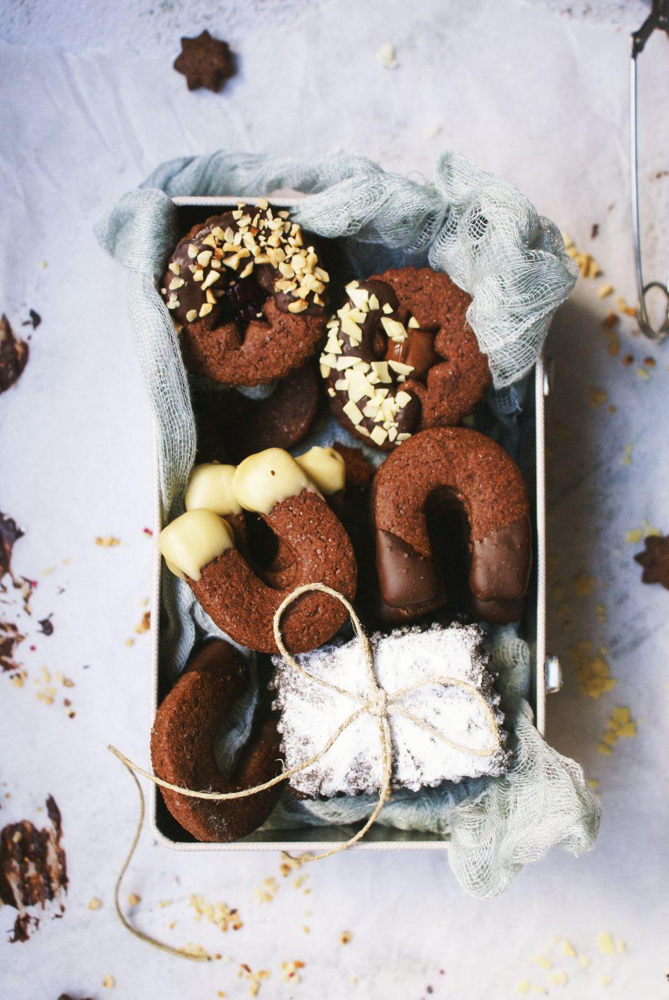 Biscotti con farina di riso e cioccolato senza glutine ripieni di crema di nocciole o marmellata di mirtilli e ricoperti di cioccolato fondente, scagliette di cioccolato bianco e granella di nocciole.