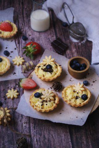 Cestini di pasta frolla senza glutine con farine naturali ripieni di crema pasticcera, mirtilli e cioccolato fondente