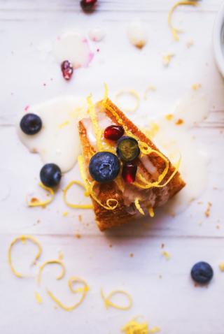Glassa di zucchero su una ciambella soffice decorata con mirtilli, melograno e scorza di limone