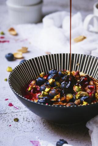 Porridge senza glutine con fiocchi di avena, mirtilli, melograno, pistacchi e  sciroppo d'acero.