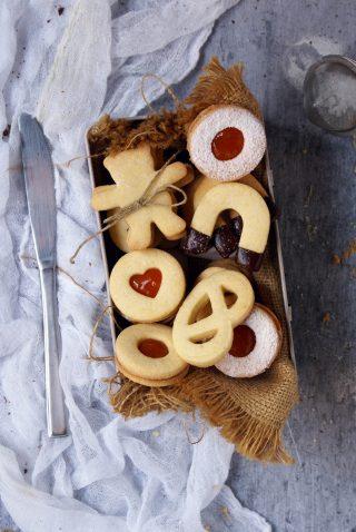 Biscotti senza glutine con farine naturali ripieni di marmellata di albicocche e ricoperti di cioccolato fondente e  zucchero a velo
