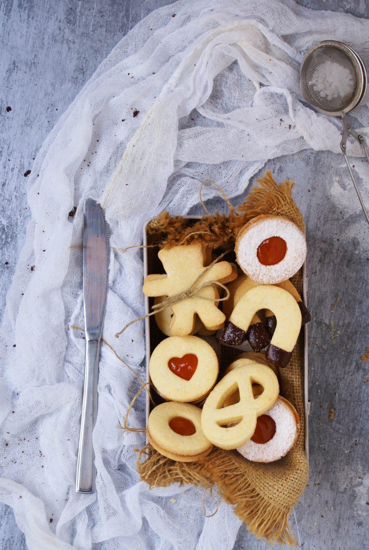 Biscotti di pasta frolla senza glutine con farine naturali ripieni di marmellata di amarene e ricoperti di cioccolato fondente e  zucchero a velo