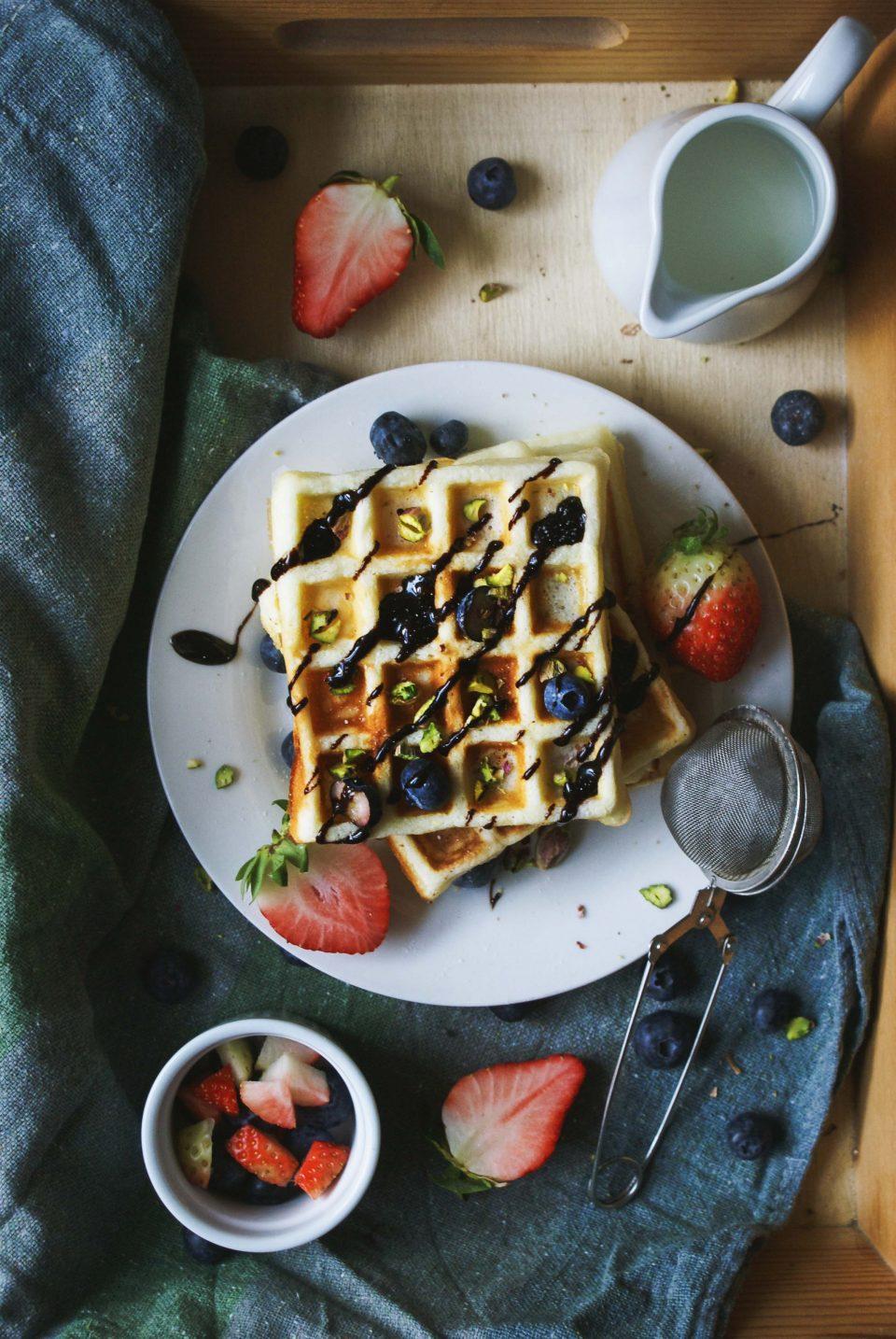 Waffle senza glutine con mirtilli, fragole, pistacchi e cioccolato fuso
