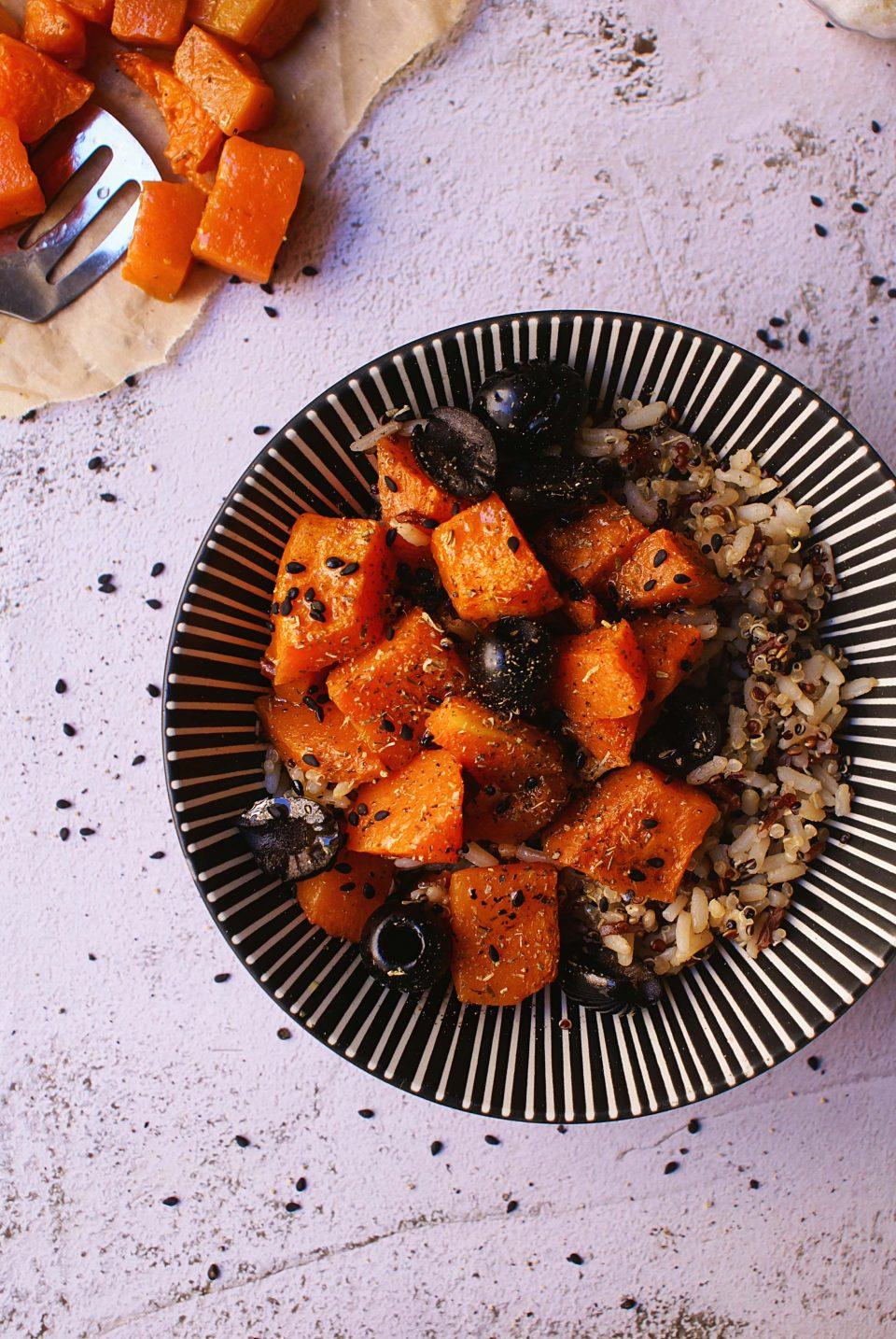 Cereali antichi con zucca aromatica e olive decorato con semi di sesamo nero