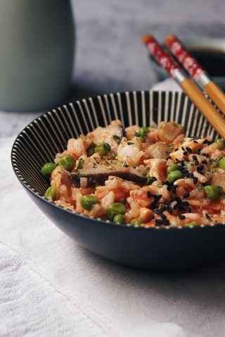 Riso con pollo, funghi, piselli e pomodoro, condito con prezzemolo e semi di sesamo nero