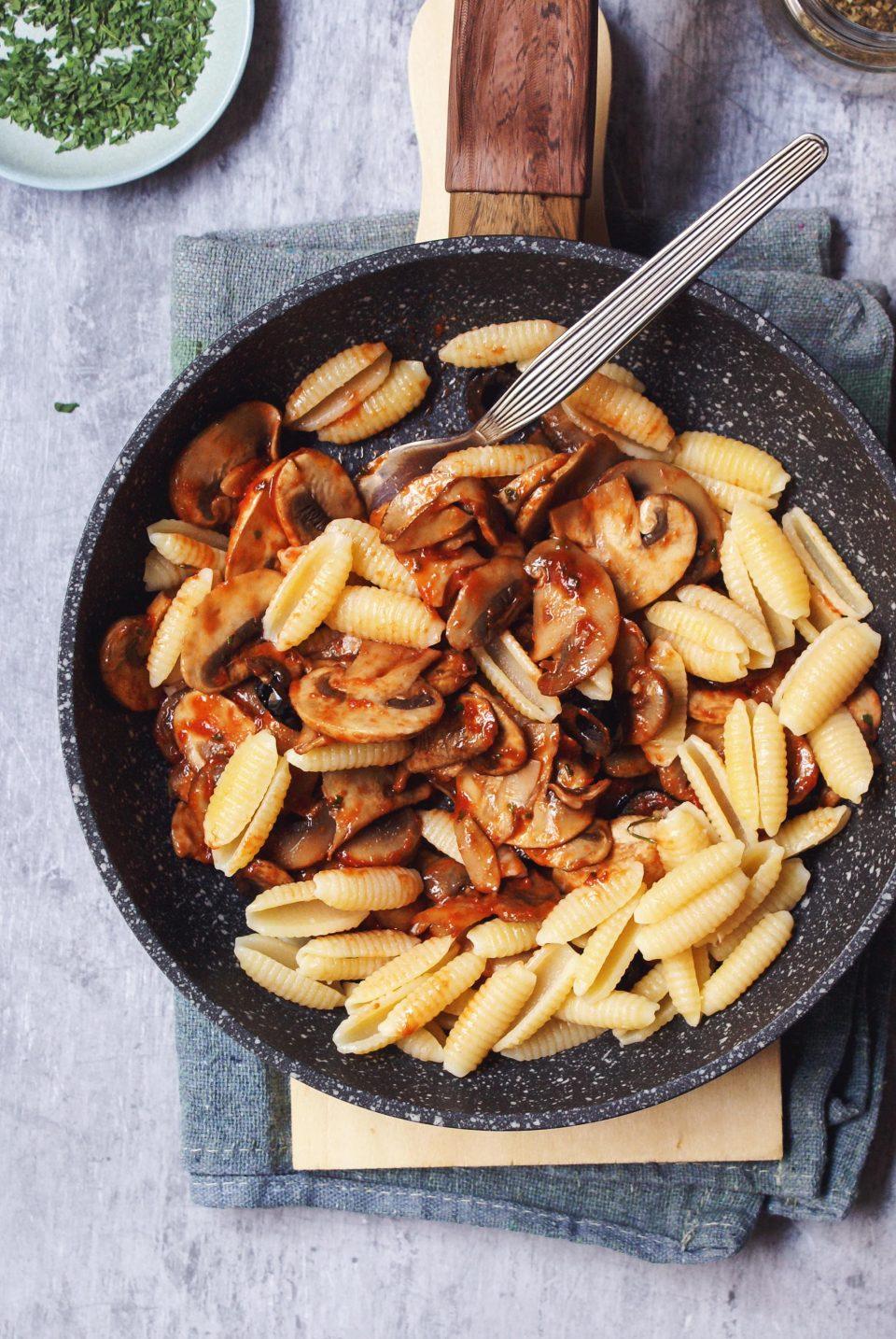 Pasta con funghi e pomodoro, olive nere e prezzemolo