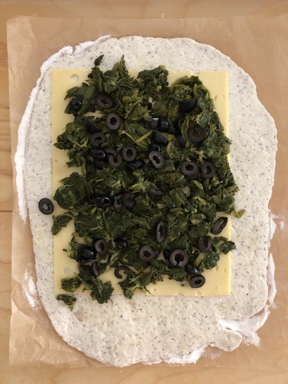 Rotolo di pizza farcito con verdura, olive e formaggio