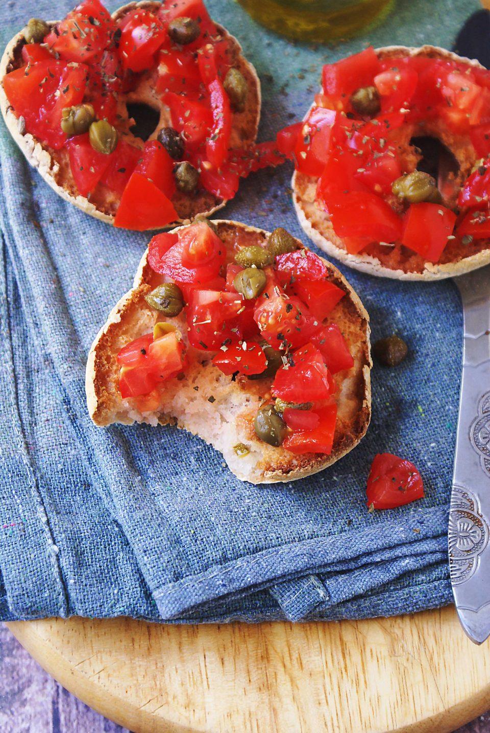 Friselle senza glutine fatte in casa con pomodorini, capperi e origano.
